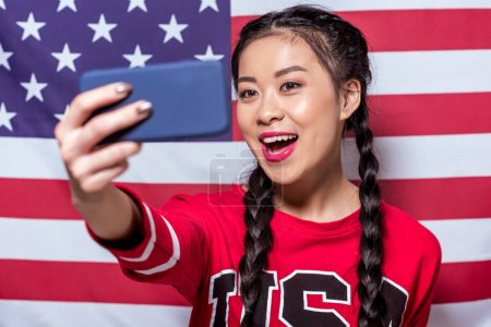 Photo for Portrait of smiling woman taking selfie on smartphone with american flag behind - Royalty Free Image