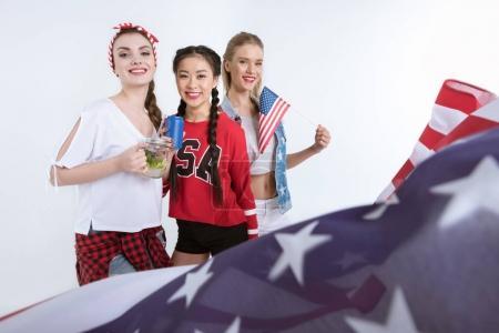 Foto de Mujeres jóvenes con la bandera de Estados Unidos mirando a cámara y consumo de bebidas, celebración del día de la independencia - Imagen libre de derechos