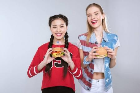 smiling multiethnic girls holding burgers