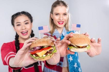 happy multiethnic women holding burgers