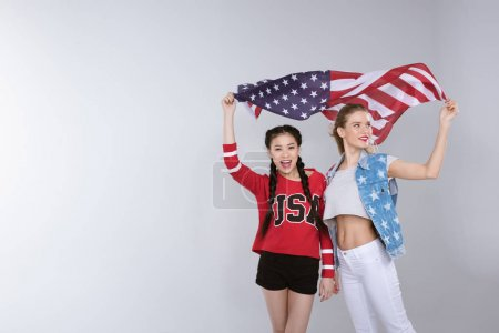 Women standing and holding flag of USA