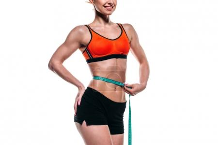 sportswoman measuring her waistline