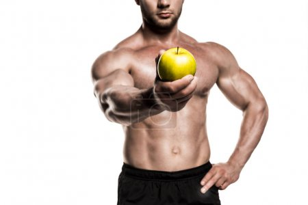 muscular sportsman holding apple