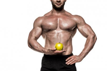 Muscular sportsman holding apple