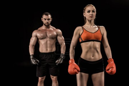 Photo for Confident muscular young sportsman and sportswoman in boxing gloves standing isolated on black - Royalty Free Image