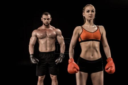 Photo pour Confiant, musclé sportif, jeune et sportive dans les gants de boxe permanent isolent sur fond noir - image libre de droit