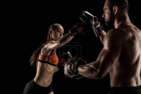 Photo pour Sport musclé jeune homme et femme boxe ensemble isolé sur noir - image libre de droit