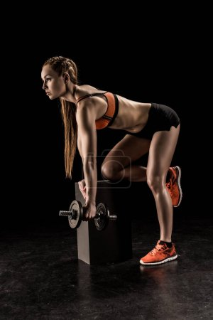 Photo for Side view of muscular young sportswoman standing on knee and exercising with dumbbell - Royalty Free Image