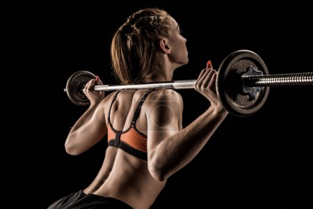 Photo for Athletic young sportswoman lifting barbell isolated on black - Royalty Free Image