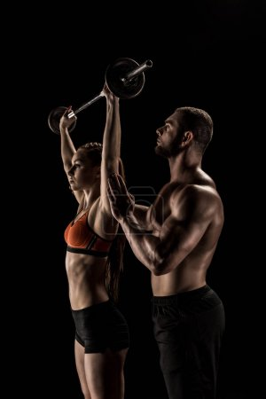 Photo for Side view of muscular trainer looking at young sportswoman lifting barbell - Royalty Free Image