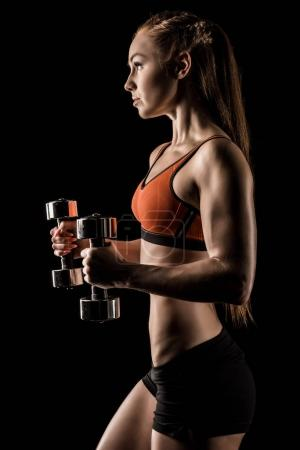 Sportswoman exercising with dumbbells