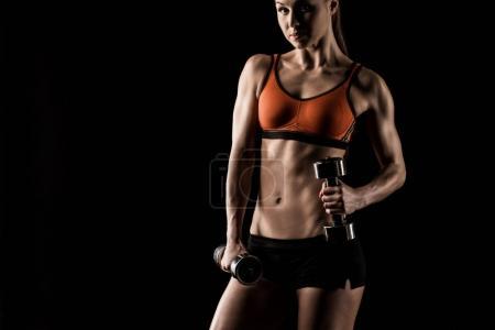 Sportswoman exercising with dumbbells