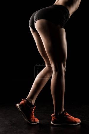 Photo pour Coup de projectile recadré de jeune sportive musclée en short et baskets debout isolé sur noir - image libre de droit