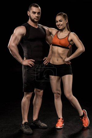 Photo for Sportive man and woman posing together and looking at camera isolated on black - Royalty Free Image