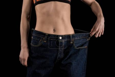 Photo for Cropped shot of woman wearing large jeans isolated on black, weight loss concept - Royalty Free Image