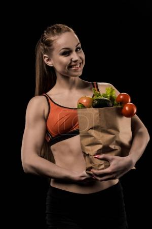 woman holding bag with vegetables