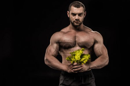 shirtless sportsman holding salad leaves