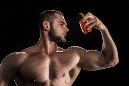 Shirtless athlete holding bell pepper