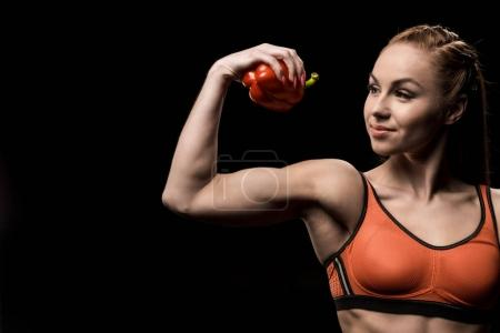 Photo for Smiling sporty girl holding bell pepper solated on black - Royalty Free Image