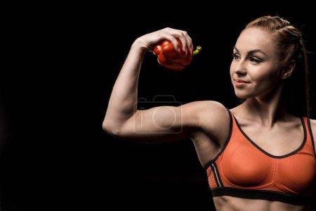Sporty girl holding bell pepper
