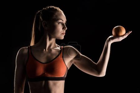 Pensive sporty girl holding orange