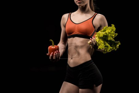 sportswoman holding bell pepper and lettuce