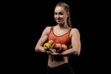 smiling caucasian sportswoman holding apples