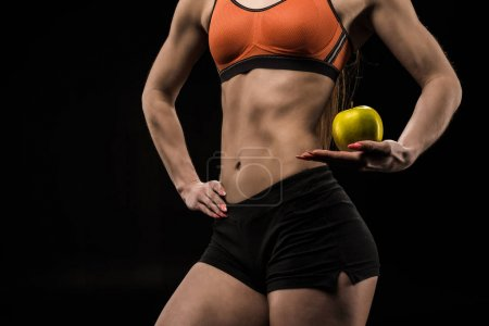 Photo for Cropped shot of sportswoman holding ripe green apple isolated on black - Royalty Free Image