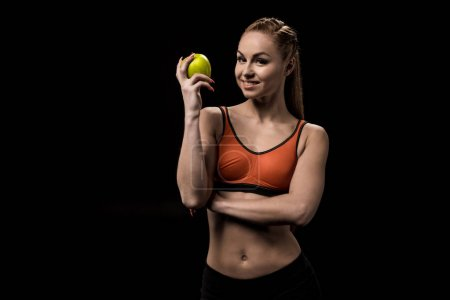 Photo for Portrait of smiling caucasian sportswoman holding green apple - Royalty Free Image