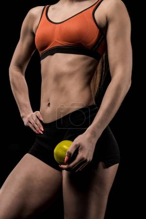 sportswoman holding ripe green apple