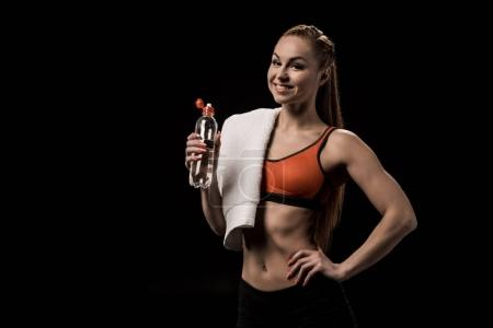 athlete with towel holding bottle of water