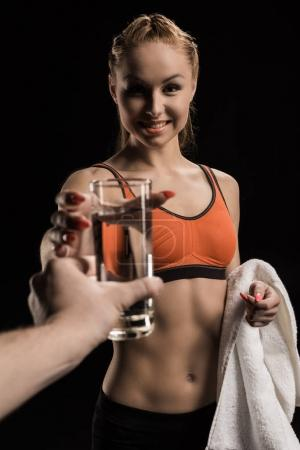 Sportswoman with towel taking glass of water