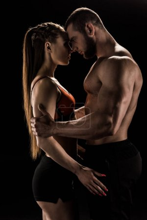 Photo for Young sensual sporty couple embracing isolated on black - Royalty Free Image
