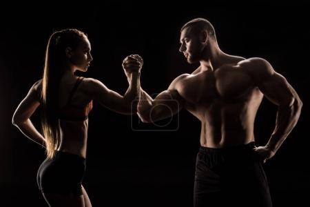 Photo for Young sporty couple holding hands isolated on black - Royalty Free Image