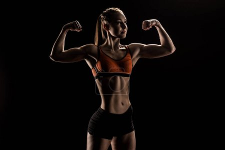 young caucasian sportswoman flexing biceps