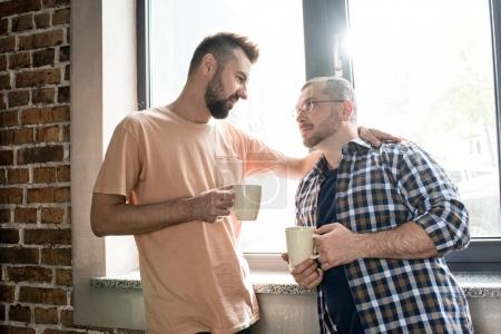 Photo for Middle aged homosexual couple holding cups of coffee and looking at each other at morning - Royalty Free Image