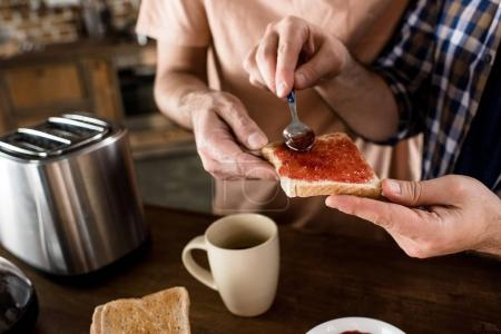 Photo for Cropped shot of men preparing toast with jam for breakfast at home - Royalty Free Image