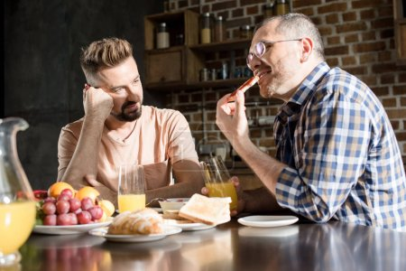 Photo for Bearded man looking at smiling partner in eyeglasses eating breakfast at home - Royalty Free Image