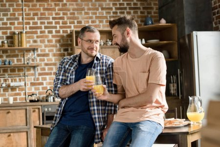 Photo for Smiling men holding glasses of orange juice and looking at each other at home - Royalty Free Image