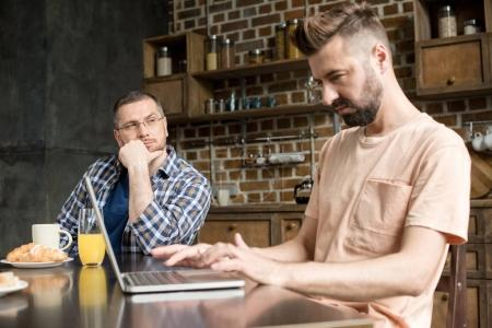 Photo for Pensive man in eyeglasses looking at bearded partner sitting at table and using laptop - Royalty Free Image