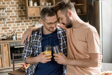 Photo for Happy gay couple standing embracing and holding glasses of juice at home - Royalty Free Image