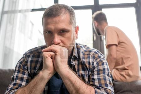 Foto de Retrato de hombre molesto casual sentado en el sofá en actitud pensativa - Imagen libre de derechos
