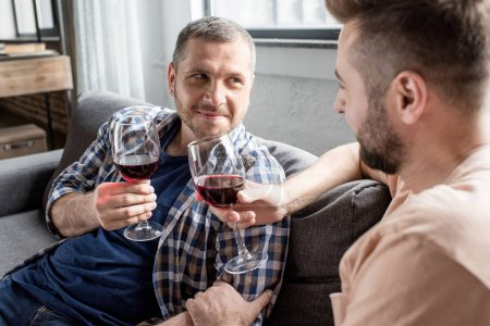 Photo for Homosexual couple drinking wine while sitting on sofa at home - Royalty Free Image