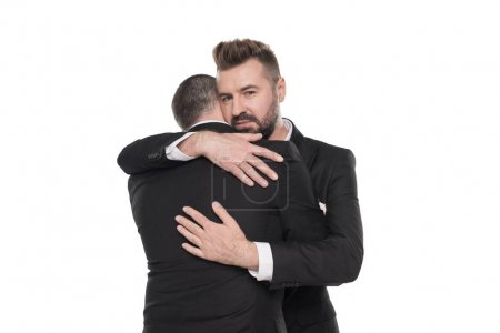 Photo for Homosexual couple of grooms in suits hugging isolated on white - Royalty Free Image