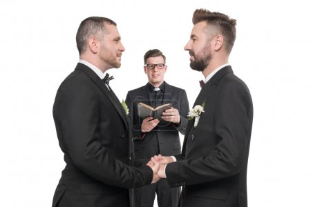 Photo for Young homosexual couple in tuxedos holding hands at wedding ceremony - Royalty Free Image