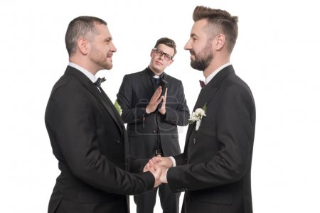 Photo for Smiling homosexual couple at suits holding hands at wedding ceremony isolated on white - Royalty Free Image