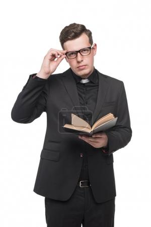 young priest reading scripture book
