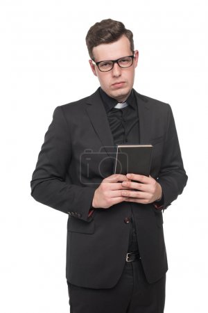 Young priest holding scripture book