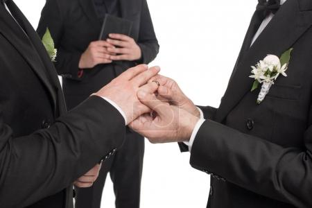 homosexual couple exchanging rings at wedding