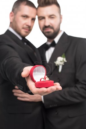 Photo for Homosexual wedding couple emracing and showing wedding rings in box - Royalty Free Image